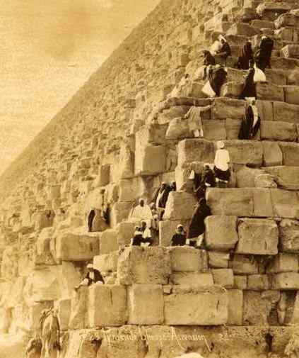 Egyptians stand on the rising courses, each stone half as tall as they are